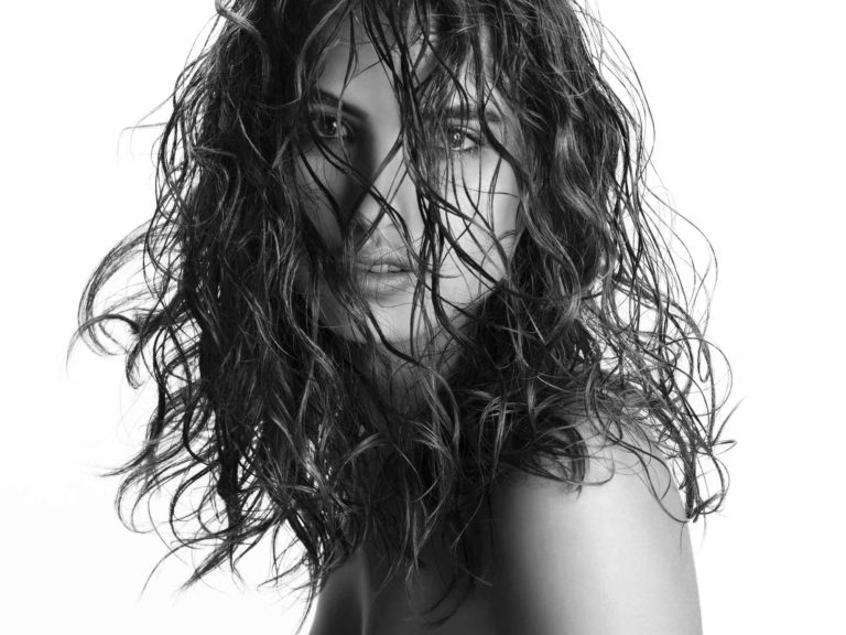 black and white photo of a beautiful woman with wavy wet hair